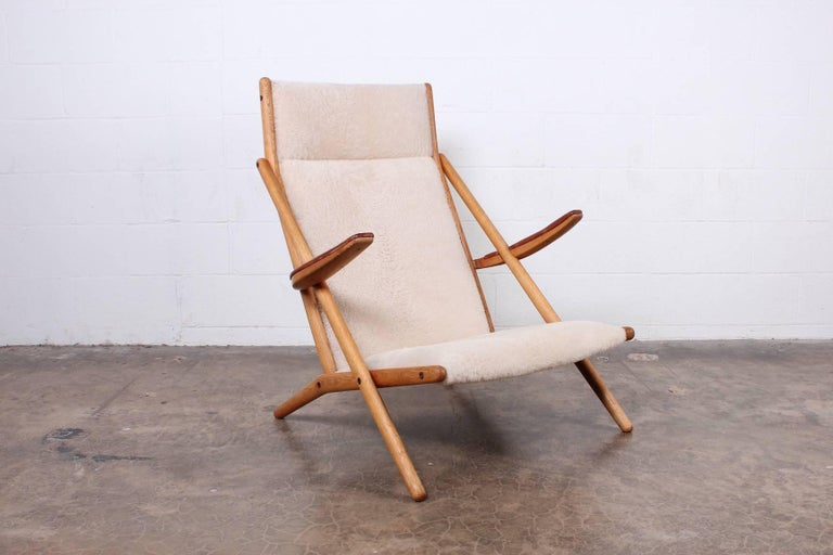 A rare oak lounge chair with brass hardware, original leather arms and sheepskin upholstery. Designed by Ditte and Adrian Heath for Soren Horn.