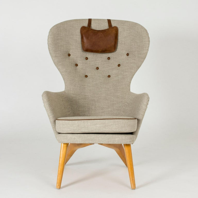 Cool lounge chair by Gustaf Hiort af Ornäs, with a tall, wide back and amazing silhouette. Brown leather piping, buttons and small neck cushion.