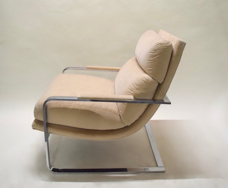 Polished chrome-plated flat-bar lounge chair with rounded corners in the front of the frame and a curved platform seat with three attached cushions and upholstered arm rests, all in a cream colored velvet. Measures: Seat height is 19 inches.
