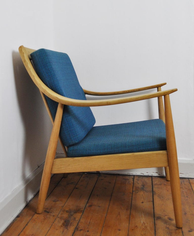 Lounge chair designed by Peter Hvidt & Orla Mølgaard-Nielsen for France & Daverkosen in Denmark in the 1950s. Frame made in elm. Backrest with seven spindles and the seat rest features vinyl-covered springs. Foam cushions upholstered in textured