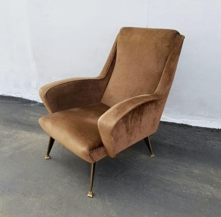 Original upholstery in coffee late color, brass legs that are special design and made for this chair. Still very comfortable and presentable.