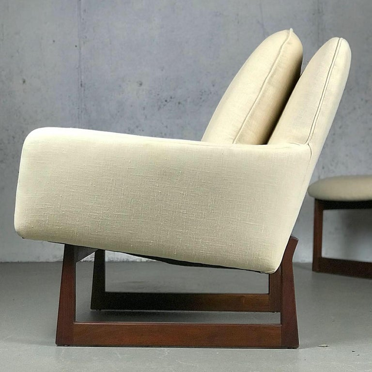 Sleek and spacious lounge chair and ottoman designed by Jens Risom for Jens Risom designs, 1960s. Walnut bases are in great condition. New cream linen upholstery and cushions. Measures: Chair 32.5