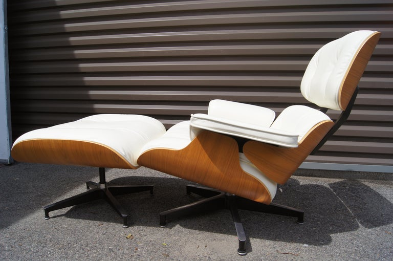 This version of Charles and Ray Eames's iconic molded plywood lounge chair for Herman Miller, model 670/671, features a walnut shell and pearl white leather upholstery. The chair's angled tilt, swiveling base, and matching ottoman offer the deepest