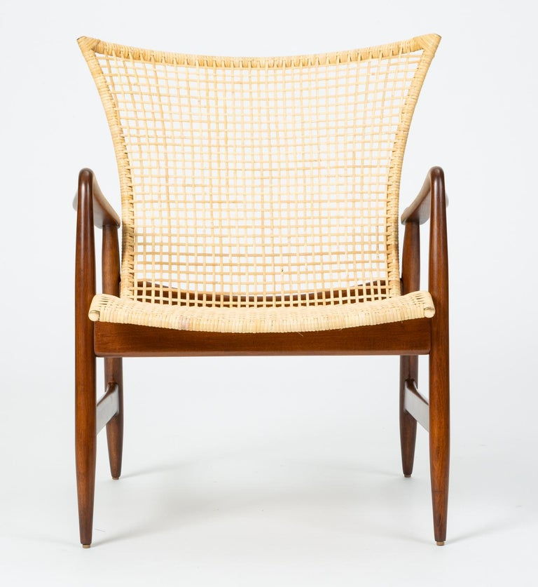 A 1958 design by Ib Kofod-Larsen for Selig, this refined lounge chair has a slight wingback design and delicately curved details. Petal shaped armrests swoop upwards into a rounded armrest with finely shaped joinery. Set into the walnut-stained