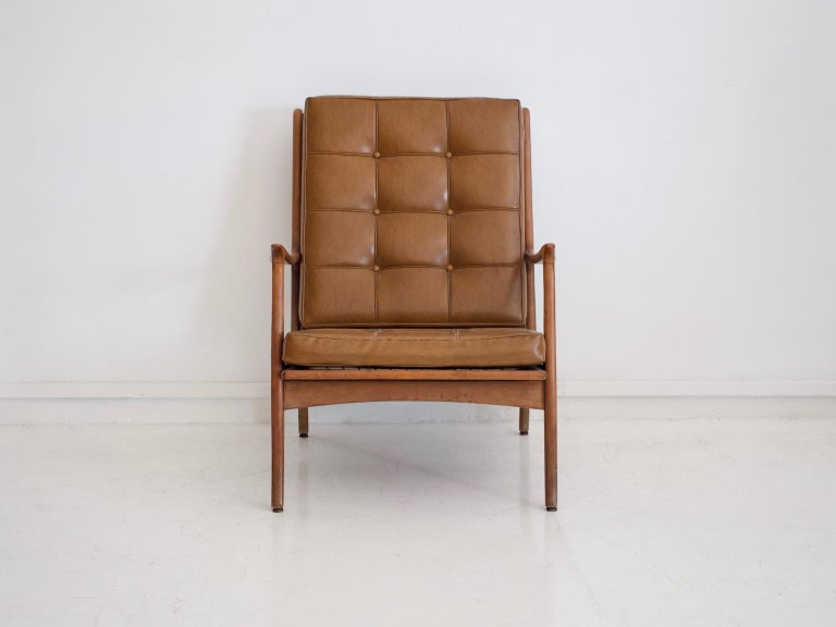 Brown leather upholstered armchair with wooden frame manufactured in Italy, circa 1960. Some age-related wear seen on the feet and frame.