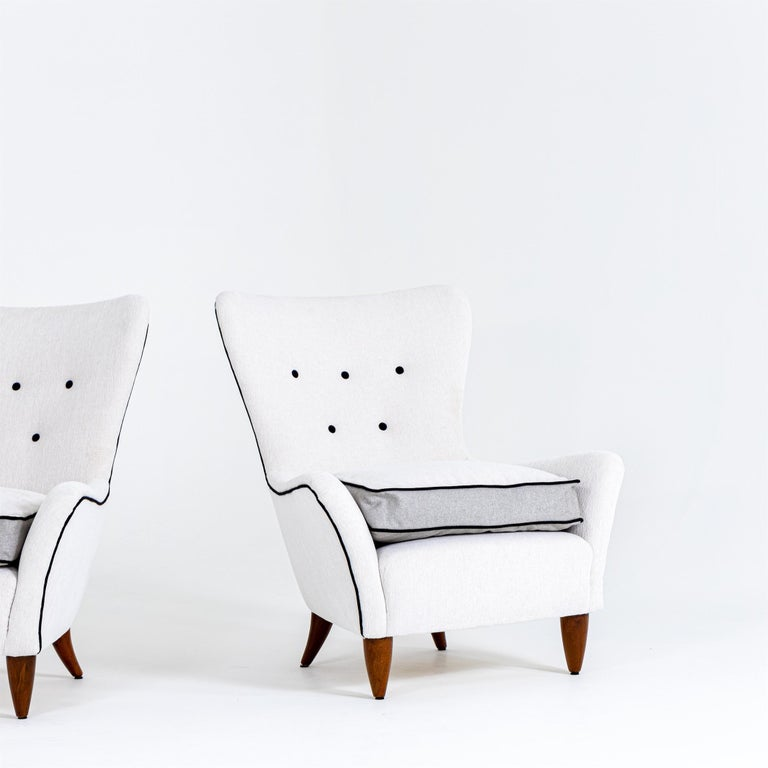 Pair of white upholstered lounge armchairs on conical legs in cherry by Brambilla. Domus 267 Feb. 1952.