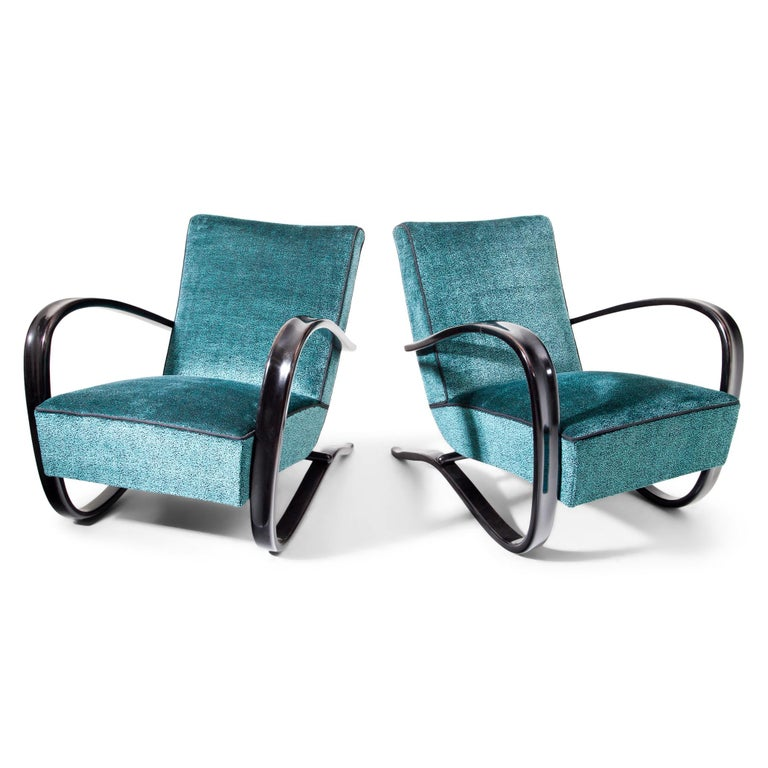 Pair of Halabala armchairs, reupholstered with blue-black mottled, high quality fabric. The dark-tinted armrests sweep in an elegant c-shape around the side of the seat cushion and become the bearing frame. The chairs were newly upholstered with a