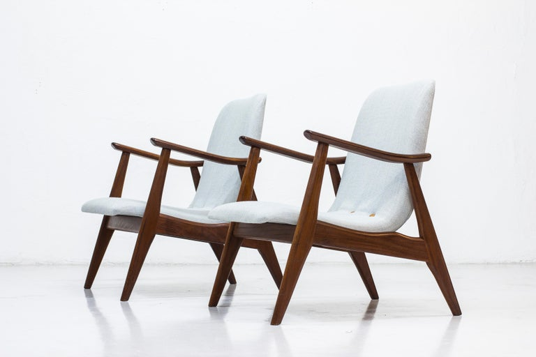 Pair of easy chairs designed by Louis Van Teeffelen. Produced in the Netherlands by WéBé during the 1950s. Frame made from solid afromosia wood and seats reupholstered in grey wool fabric with leather buttons. Good vintage condition with age related