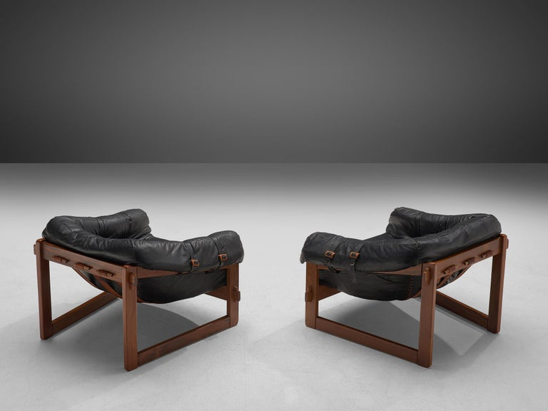 Percival Lafer, pair of lounge chairs, leather and wood, Brazil, 1960s  Bulky and grand lounge chairs by Brazilian designer Percival Lafer. This set features a solid dark wooden base with leather straps spanned between the slats. The tufted leather