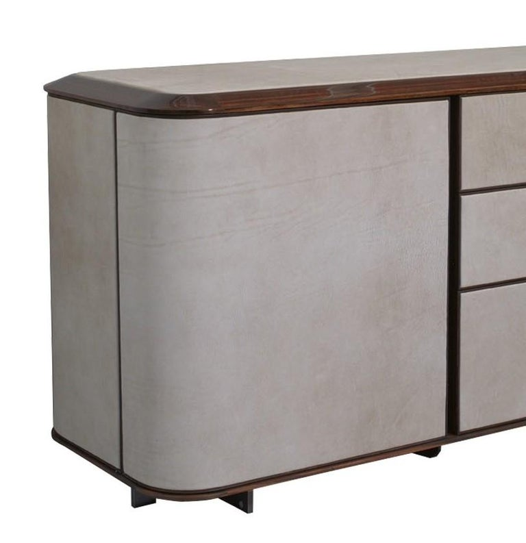 Part of the Love collection that features wood upholstered with light-colored leather, this sideboard features a wood structure in the shape of an elongated rectangular with the Ulivi's signature round corners. The side doors and the panels of the