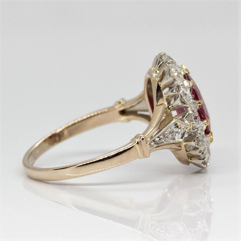 Crafted in 18k gold and platinum, this lovely item displays a central natural oval cut GIA CERTIFIED ruby that weighs 2.45ctw. Surrounded the prominent central stone and encrusted on the sides, this ring displays 14 old mine cut diamonds of G-VS2