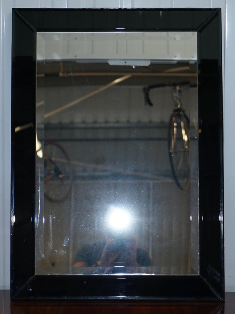 We are delighted to offer for sale this nice beveled edge glass mirror with black glass frame and velvet finish back  A good looking and well made decorative mirror, apart from one corner chip of glass missing the mirror looks perfect to me  Its