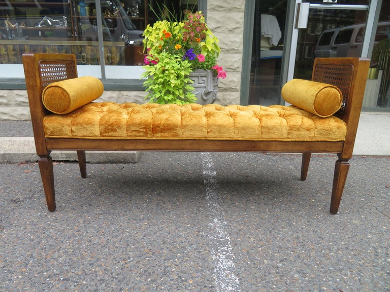 Lovely caned walnut bench with original tufted gold velvet upholstery. We love the original cylinder pillows that flank each end along with the lightly distressed original finish.