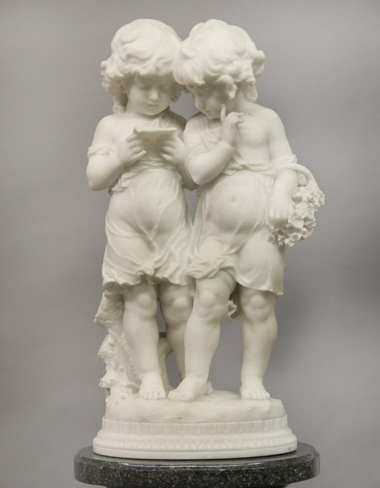 A lovely early 20th century Italian Carrara marble sculpture of two sisters by Affortunato Gory  Depicting two little girls reading, one with a basket of flowers, standing on a oval carved base  Inscribed A. Gory  Affortunato Gory 1895-1925