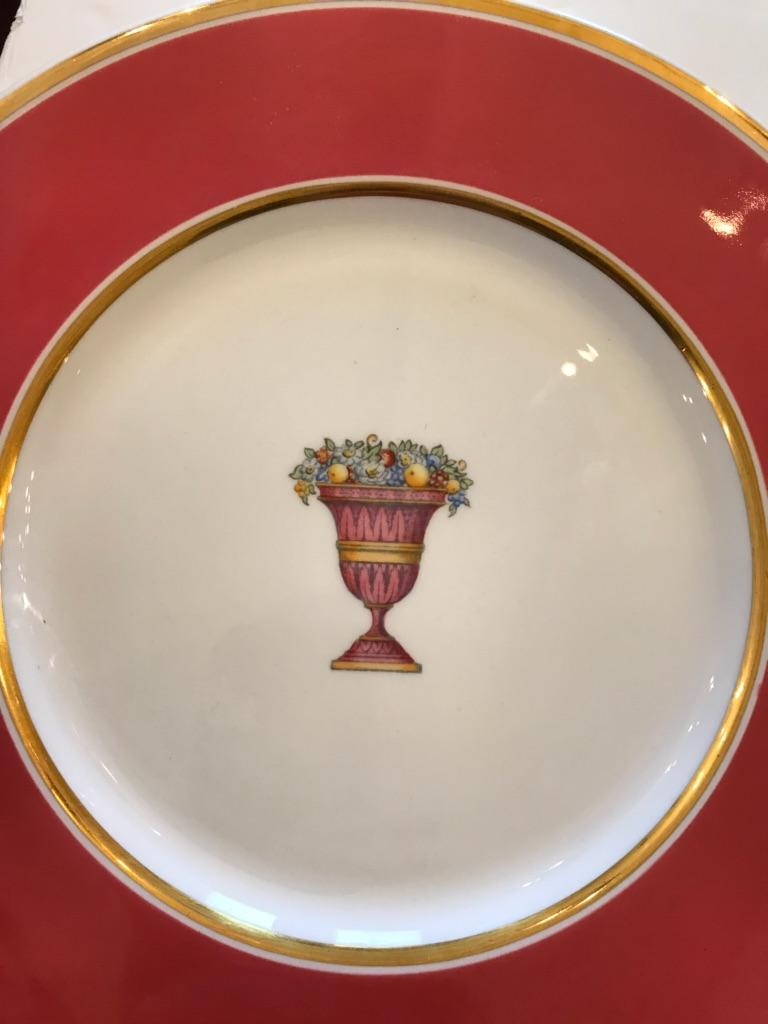A set of 12 beautiful rouge and gold service plates having a central urn with flowers. 