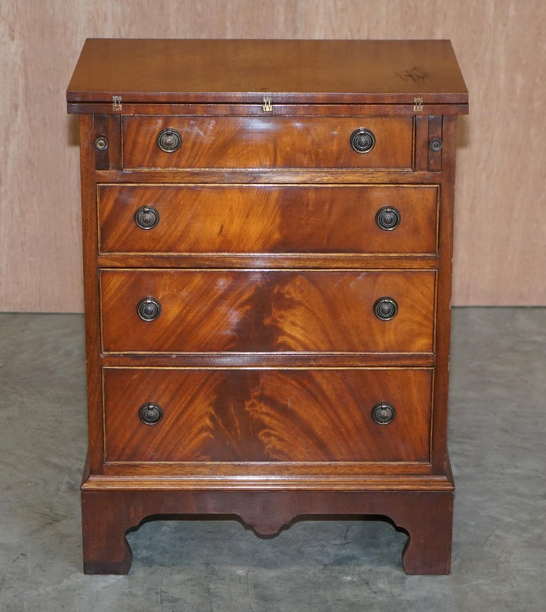 We are delighted to this stunning flamed mahogany bachelor's chest of drawers with folding butlers shelf  A very good looking well-made and functional piece of furniture. It as for all intents and purposes a Georgian style chest of drawers however
