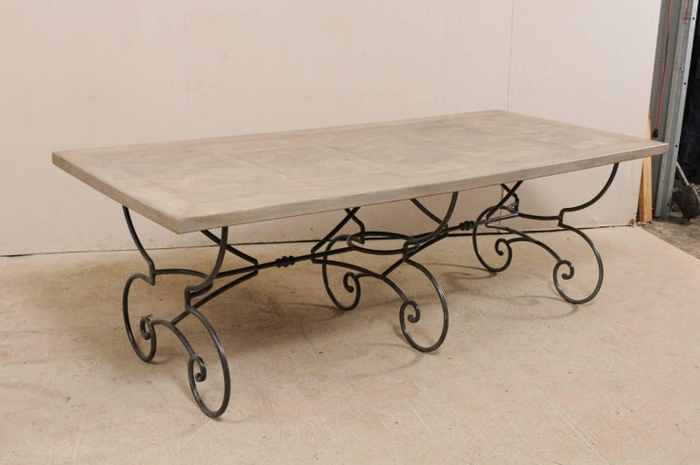 A French mid-20th century wood top table with scrolling iron base. This French vintage table features an inlay wood top, decorated with geometrical patterns framed within its centre, resting upon an ornate iron base. The base of the table is