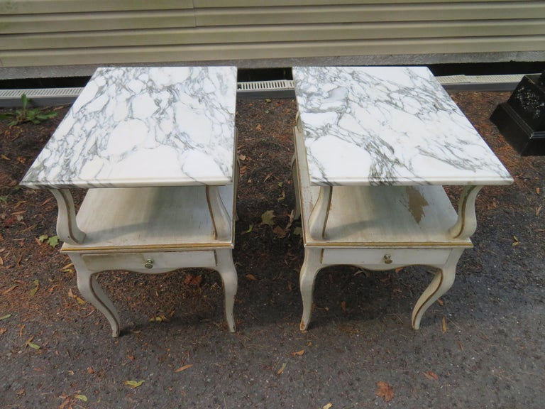 Lovely pair of Dorothy Draper style marble-top nightstands with one-drawer each. The original creamy white finish is intentionally distressed and has gold accents.
