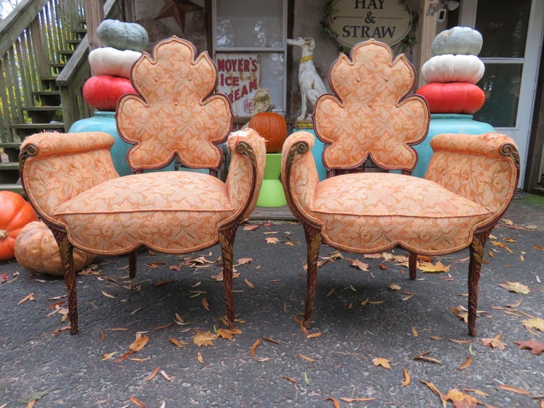 A spectacular pair of Grosfeld House chairs featuring a flower shaped backrest, channeled arms and an intricate carved wooden frame. A rare and completely stunning pair of chairs from the prestigious design house, 1940s. The original fabric does