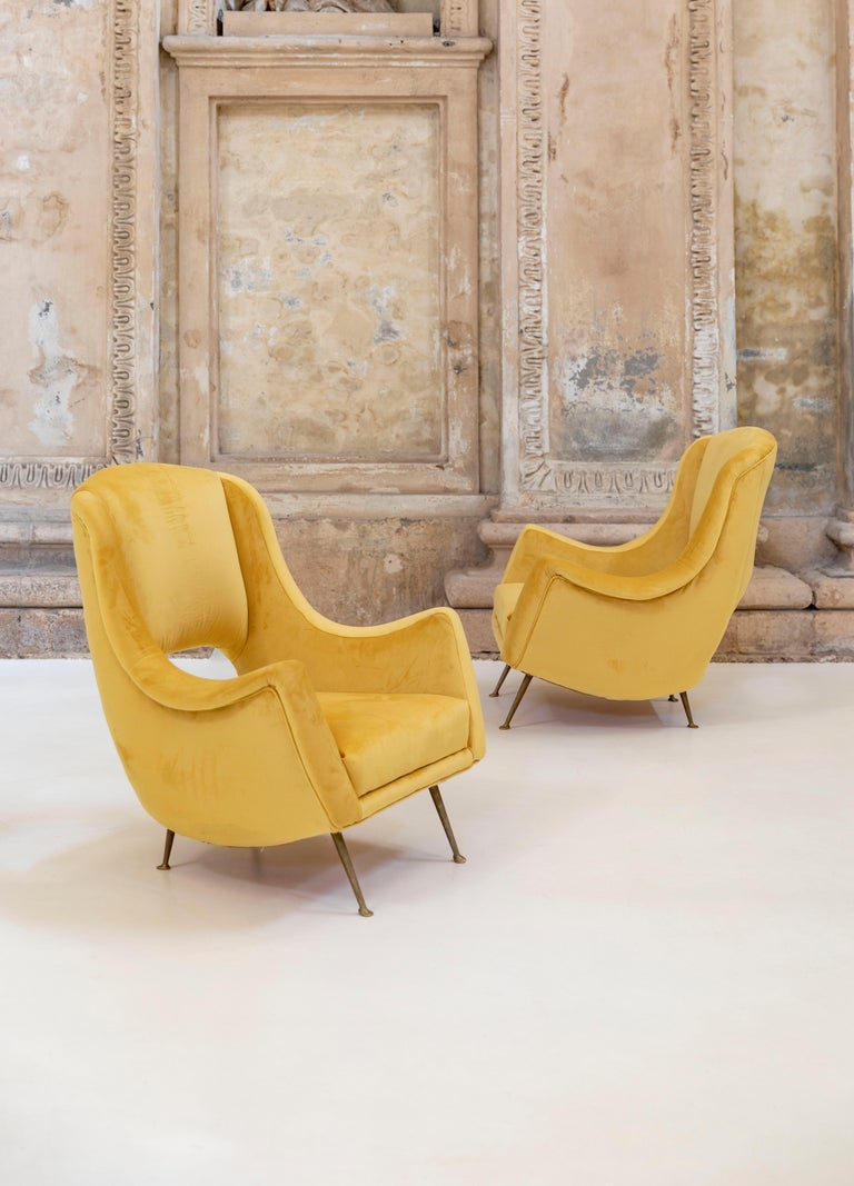 Lovely pair of armchairs attributed to Carlo de Carli.  Solid brass legs and elegant yellow velvet upholstery.  Newly reupholstered.  Shaped and open back seat.