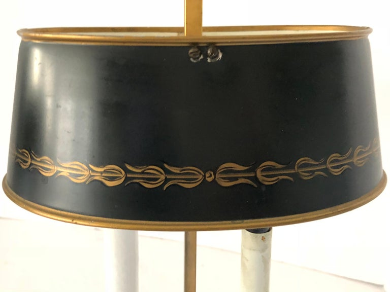 Stunning pair of French bouillotte lamps having two arms (each). The lamps are made of heavy brass that has been gold plated. They each have a black tole shade that is decorated with gold leaf around the bottom. Shades can be raised and lowered.