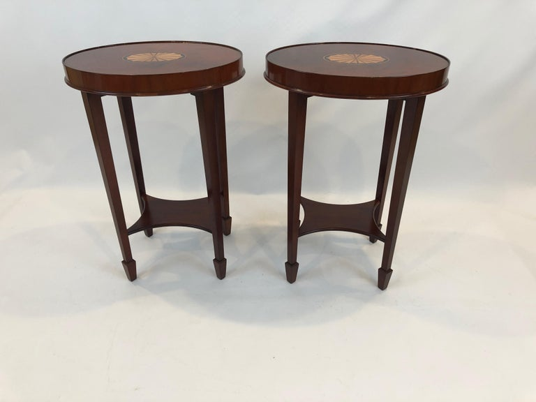 A gorgeous pair of flame mahogany oval side or end tables having ebony and satinwood central fan inlays, small bottom tier and handsome tapered legs with arrow shaped feet.