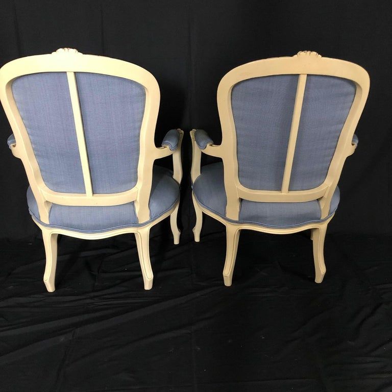 Classic pair of painted cream Louis XV style bergère armchairs upholstered in a subtle blue linen cotton blend having carved cabriole legs, floral and scrolled apron topped with floral design at top of backrest and windowpane pretty reverse. 