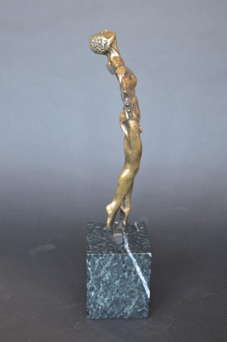 A bronze sculpture of a nude male with outstretched arms. Signed on the inner left leg, dated 1997, numbered 23/100.