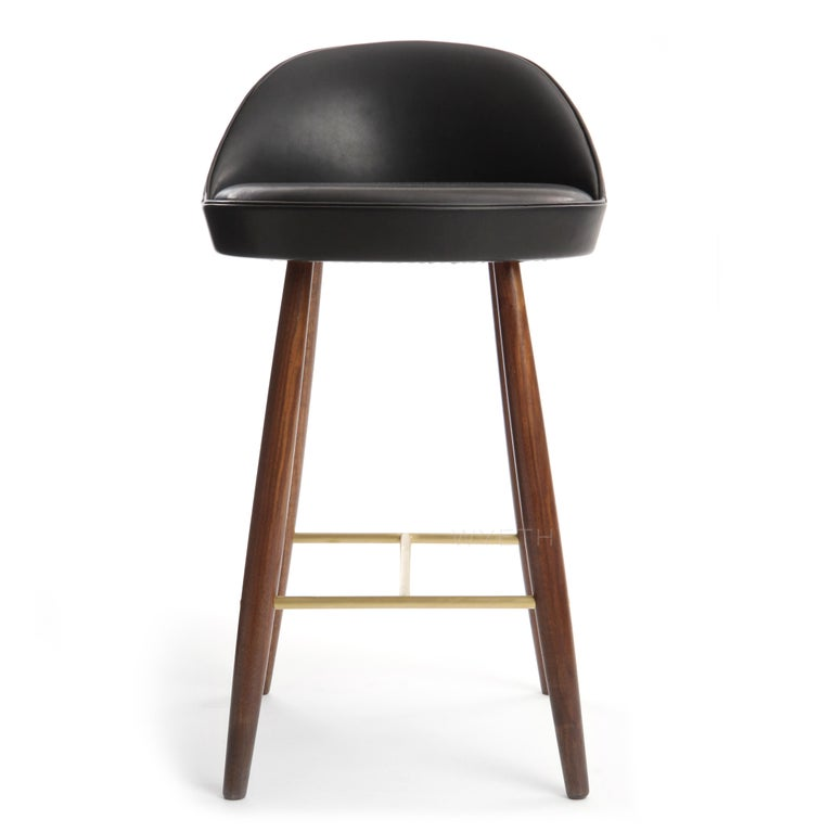 A bar stool having a sculptural low backed seat with leather upholstery, floating on solid turned walnut dowel legs conjoined by H-shaped bronze stretchers.