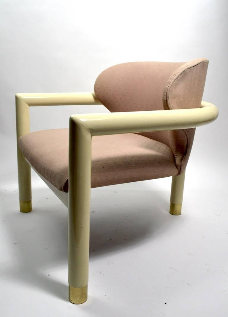 Great Art Deco Revival low slung lounge chair with cream lacquer frame, brass feet, and upholstered seat and back. The chair is in very good condition, showing only light cosmetic wear, normal and consistent with age, with exception of the fabric