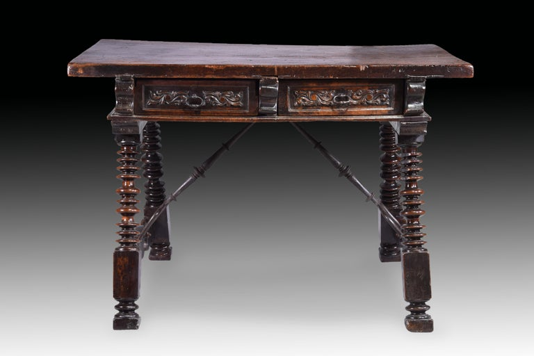 Stage table with hairpin clips. Walnut wood, wrought iron. Spain, 17th century.  Low table made of carved and turned walnut wood with four A-legs, two wrought iron hairpin clips and drawers on both fronts (a total of four) decorated with