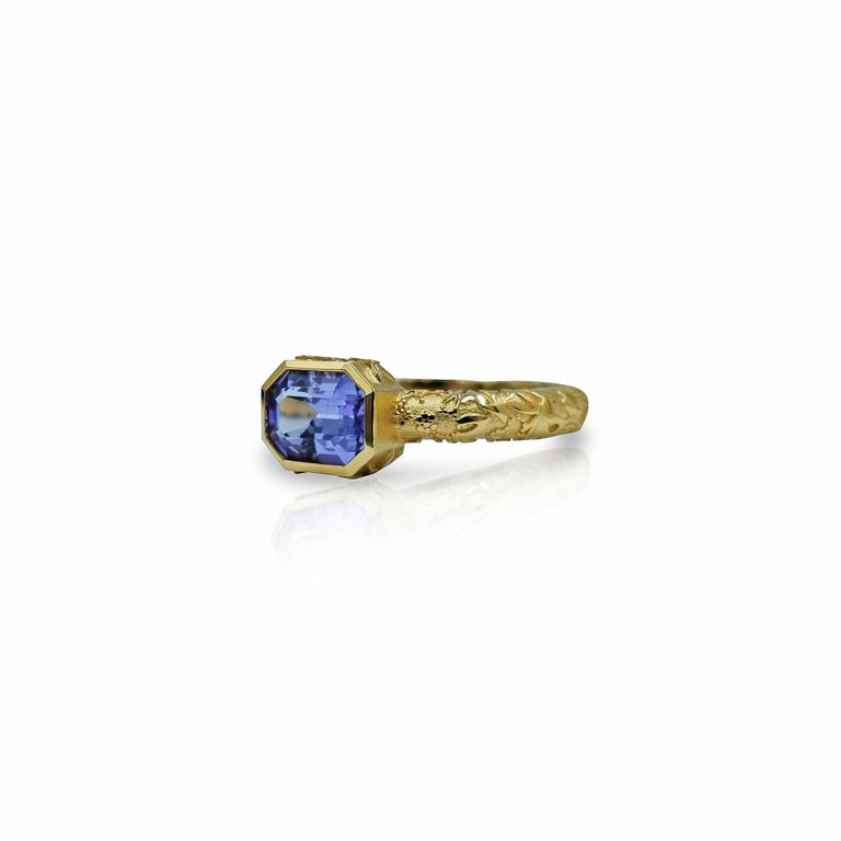 Lavender Jardin  Made of 18ct yellow gold this ornate ring is set with a stunning purple sapphire and the band features the signature Luca Jouel floral motif.     1 x rectangular step cut sapphire: medium purple colour, clean stone, bright and