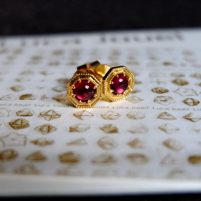 La Lune Rouge  The perfect accoutrement, these sweet deco-inspired stud earrings in 18ct yellow gold feature a pair of beautiful rhodolite garnets in settings complimented by milgrain details.  2 x round cabochon rhodolite garnets: deep