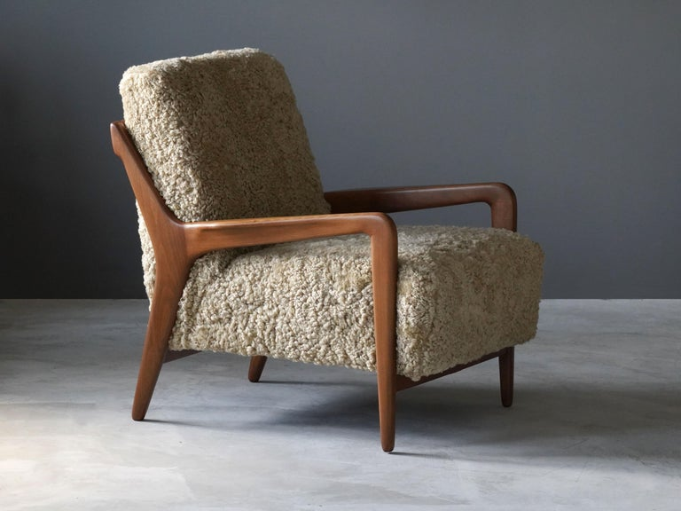A lounge chair produced by Lucchini & Lissone, Italy, 1950s. The organically sculpted beech frame is paired with the overstuffed seat, with its softness further enhanced by sheepskin upholstery. 