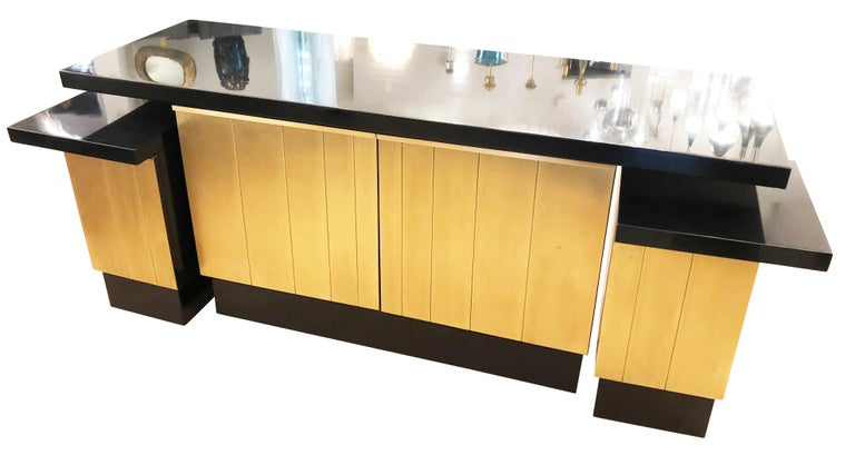 Rare console or cabinet set by Luciano Frigerio composed of a large central console and two smaller cabinets which can be used with the larger piece or interdependently. All pieces feature black lacquered tops and brushed brass paneling on the