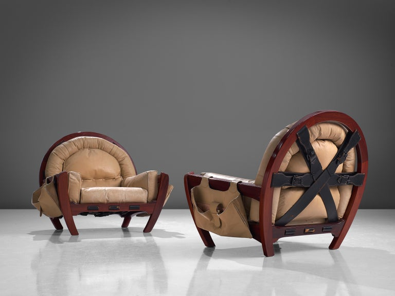 Luciano Frigerio, pair of lounge chairs model 'Rancero', mahogany, leather, Italy, 1970s  A pair of 'Rancero' lounge chairs with red stained wooden frames, designed by the Italian designer Luciano Frigerio. This model is also called 'The Throne