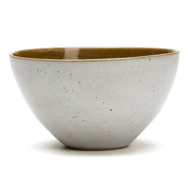 A stunning vintage British studio pottery bowl by Lucie Rie and Hans Coper, finely thrown the outer body decorated in oatmeal glaze with a dark mustard glaze to the inside bowl. The rounded bowl is slightly 'squeezed' in shape and stands on a narrow