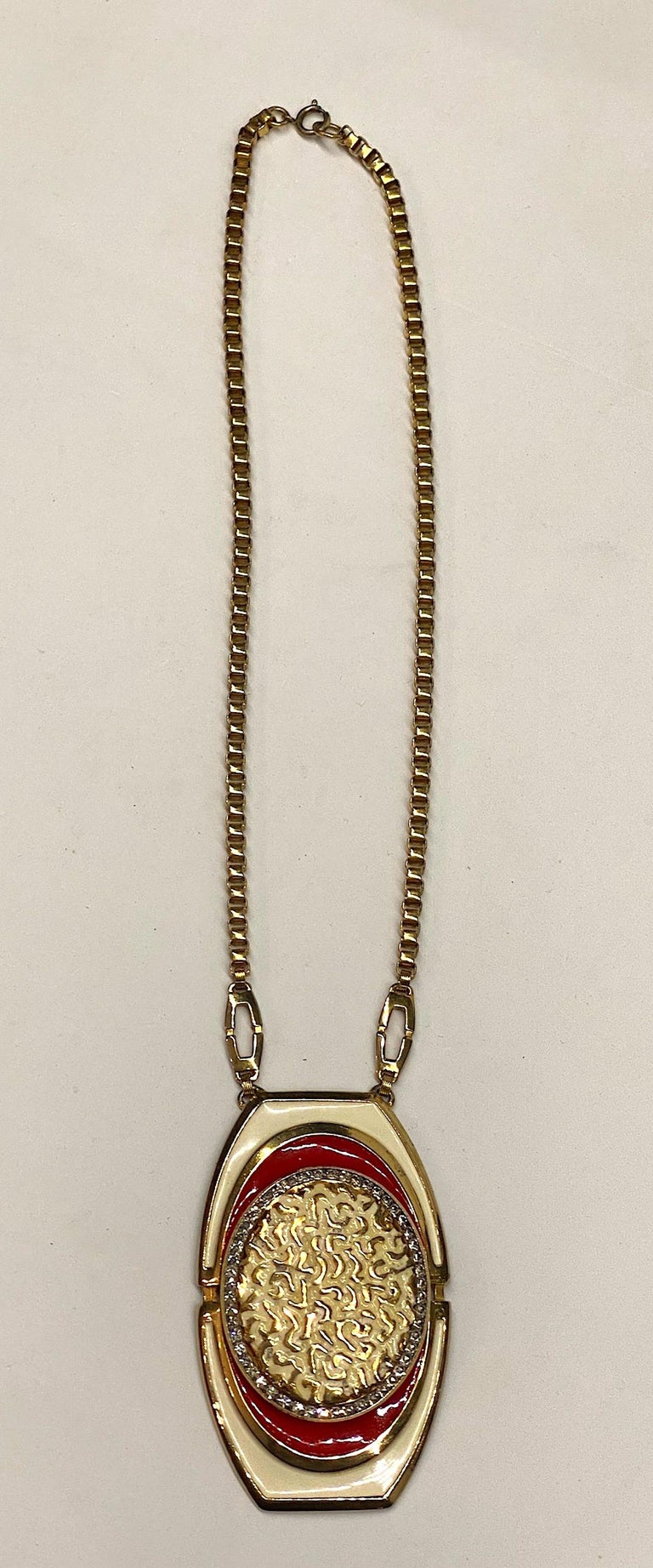 Lucien Piccard 1970s enamel and gold tone pendant necklace. A large cast pendant 2.13 inches wide and 3.5 inches long is suspended from two .88 long oval links and a thick box link chain. The pendant is enameled in an off white and red enamel. The