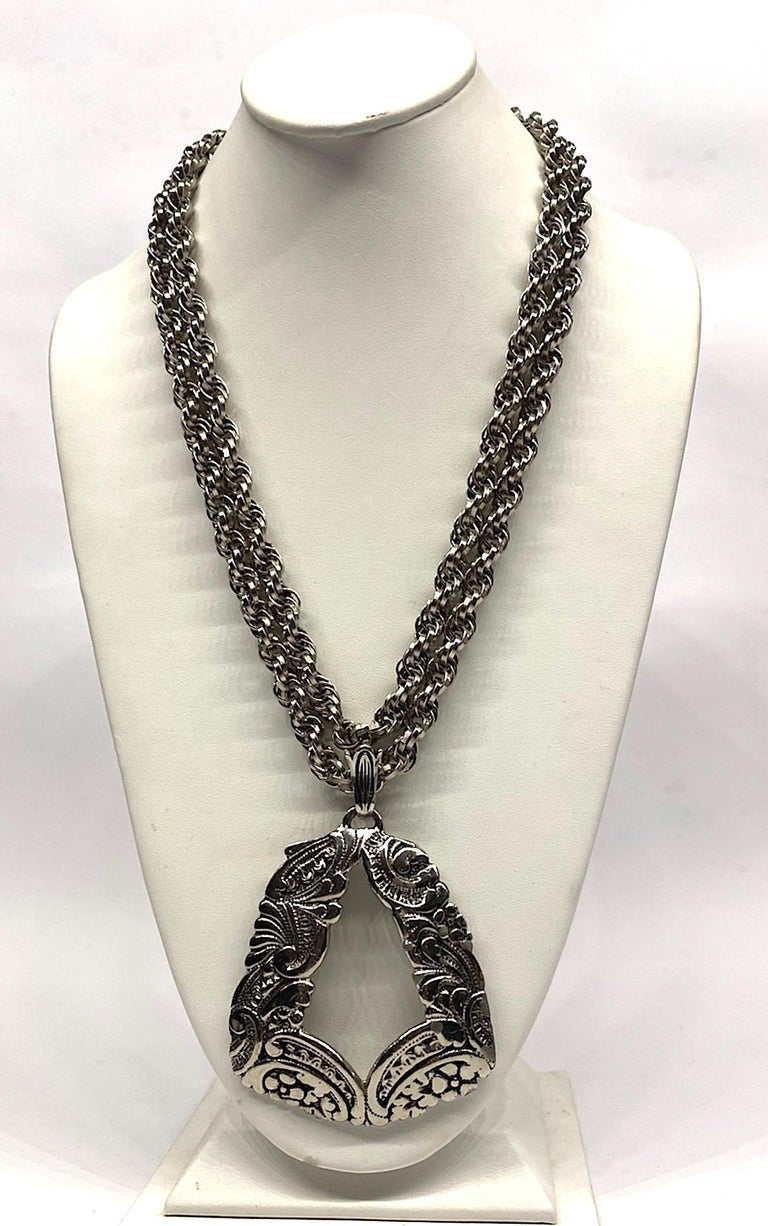 A vintage Lucien Pieccard 1970s statement pendant necklace. The two rope chains and pendant are rhodium plate in an antique silver color. The two rope link strands are .38 of an inch in diameter and meet at a satin silver color round push pin box