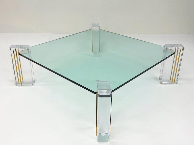 "A glamorous Lucite and brass inlay with glass top Cocktail table designed by Karl Springer in the 1980s. The table has new 3/4"" thick glass top and the acrylic legs have been newly professionally polished. 