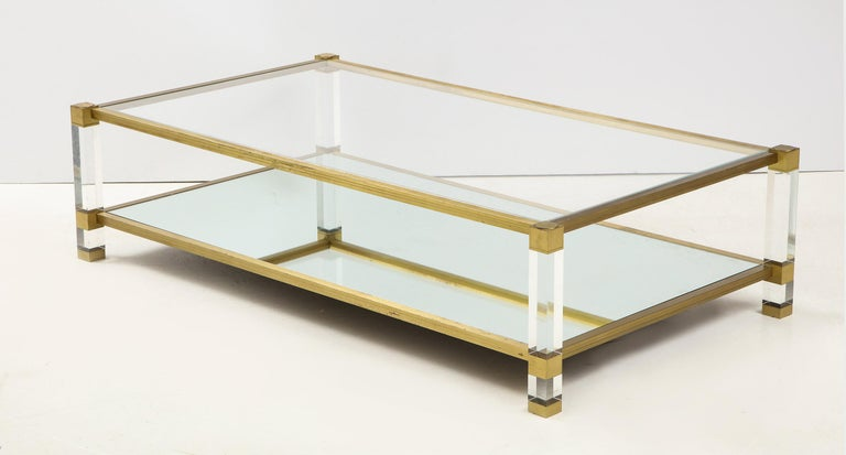 A large French Mid-Century Modern, two tier cocktail table in Lucite and brass by Pierre Vandel. The rectangular form with top section inset with glass and the lower inset with mirror.