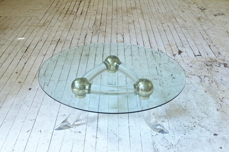 Playful little table in Lucite and brass with three splayed