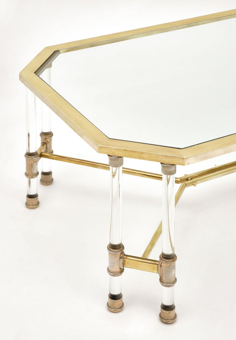 Coffee table, French, of Lucite and brass featuring a gilt brass structure with double Lucite columns in each corner. There is a brass stretcher and glass top.