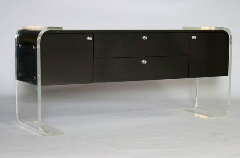 1970s lacquered charcoal gray wood buffet on a thick Lucite frame in the style of Pace or Milo Baughman. Features two cabinets and two pull-out drawers with wood interiors and original Lucite hardware. Both the cabinet and the Lucite in very good