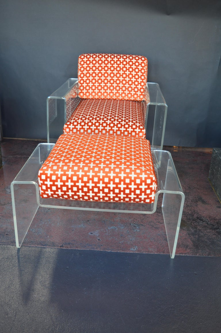 Mid-Century Modern Lucite armchair with matching Lucite ottoman. Ottoman measures: 18 inches H x 30.25 inches W x 20.