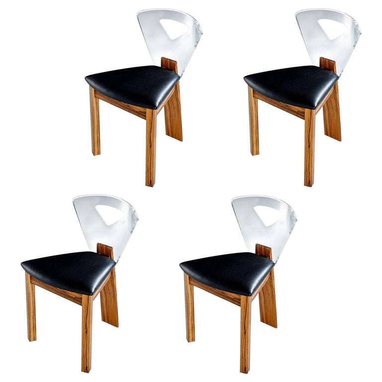 Every aspect of this set of chairs is exquisite. The chairs are unmarked and the unique construction hints that these may be a limited edition or one-off custom creation. This set consists of four side chairs. The bases are made of solid zebra wood.