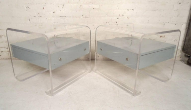 Mid-Century Modern style nightstands with grey or blue lacquer drawers and clear Lucite frames. 