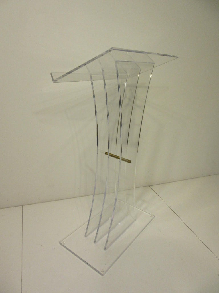 A very sculptural Lucite and brass lectern podium or hostess stand, this high end piece has three graduating uprights with a work surface having a stop to the bottom edge of the surface. The stand has a polish brass rod holding the uprights together