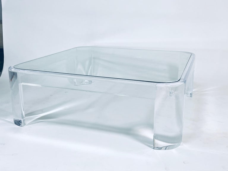 Thick lucite coffee table with rounded radius corners and flush mounted glass top by Les Prismatiques, circa 1970s.