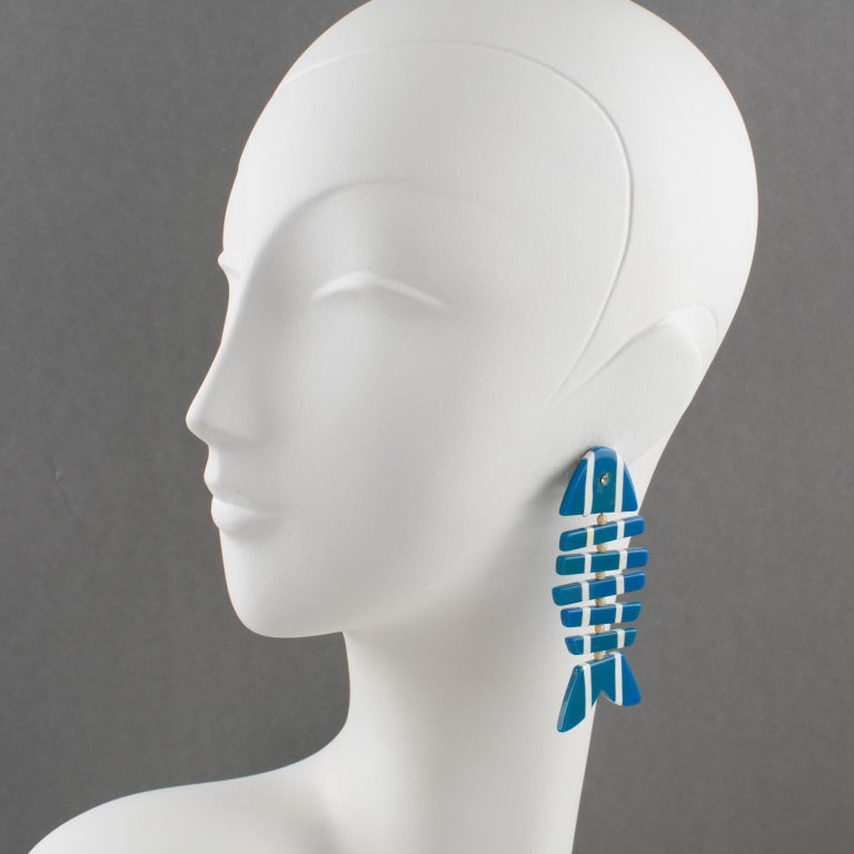 Stunning Lucite clip-on earrings, featuring a dangling geometric fishbone shape, in blue and white striped pattern ornate with crystal rhinestone eye and white glass bead spacers. No visible maker's mark. Measurements: 3.19 in. long (8 cm) x 1.38
